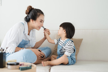 Cute little girl and her beautiful mother are doing makeup while sitting on couch at home