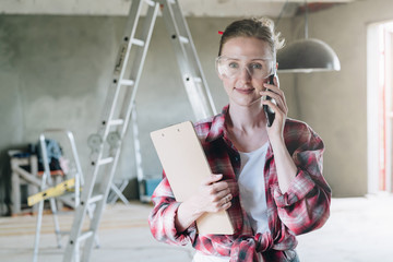 Young smiling businesswoman builder, engineer, architect, designer in construction glasses is standing