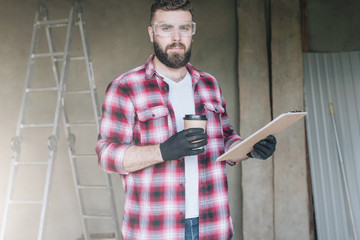 Young bearded hipster man,builder, repairman, carpenter, architect, designer dressed in plaid shirt, goggles