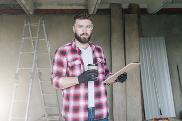 Young bearded businessman, builder, repairman, carpenter, architect, designer dressed in plaid shirt, goggles and gloves