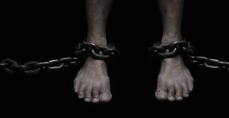 Victim, Slave, Prisoner male foor tied by big metal chain. People have no freedom concept image.