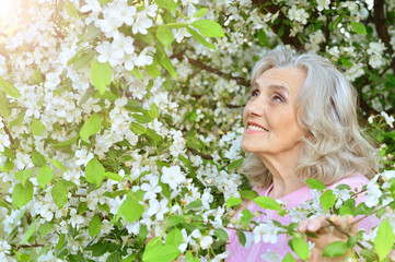 senior woman near blooming tree