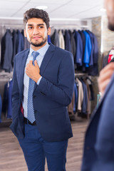Smiling man is trying on tie in front of the mirror