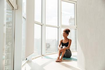Young woman in sportswear posing near wall