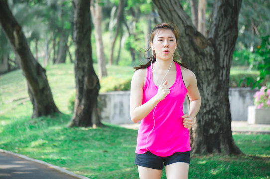 Asian sport woman running / jogging in park for health