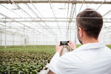 Back view of man making photo of greenery