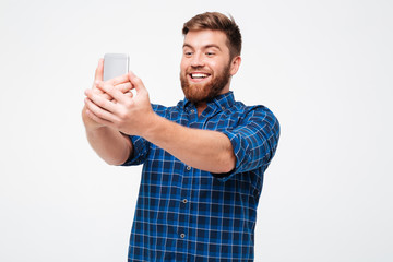 Picture of smiling bearded man in checkered shirt making selfie