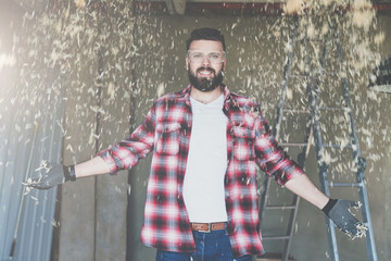 Young happy bearded man hipster carpenter in construction glasses stands in workshop. From above fly sawdust.