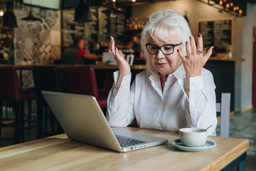 Businesswoman is sitting at a table in front of a laptop, holding her hands up and looking at monitor with astonishment