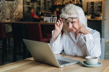 Businesswoman sits at table in front of laptop and looks closely at monitor, raising her glasses. Education for adults. Pensioner