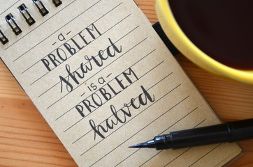 A PROBLEM SHARED IS A PROBLEM HALVED hand lettered in notebook
