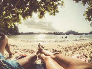 legs of romantic couple relaxing on a sandy tropical beach, Monkey island, Lan Ha bay, Vietnam - holiday concept