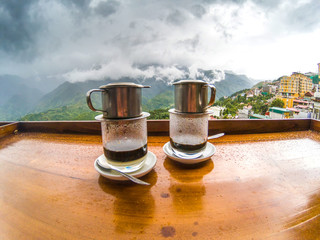 enjoying hot vietnamese black coffee on a restaurant terrace in Sapa