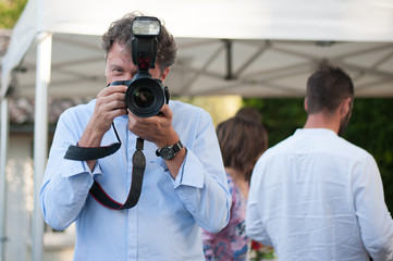 A wedding photographer takes pictures in action