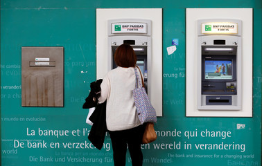 Woman withdraws money from a cash machine at an office of financial group BNP Paribas Fortis in central Brussels