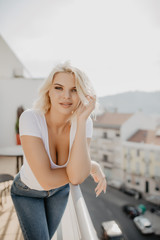 Young blonde woman sitting and relaxing at terrace on chair with city view. Fresh air in the morning of weekend or free day.