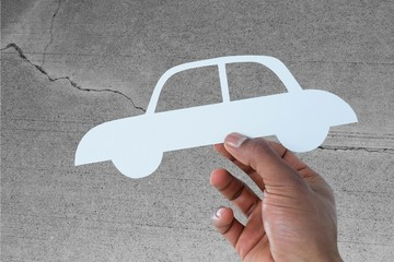 Composite image of hand holding a car in paper