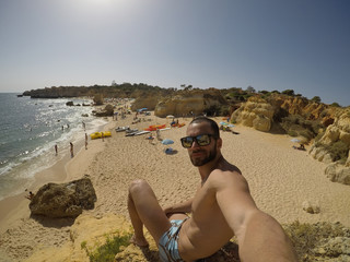 Young man taking a picture in a beach, Algarve, Portugal