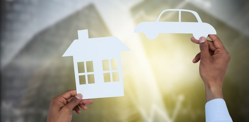 Composite image of man holding a car and a house in paper