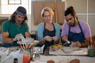 Teacher with students making clay products