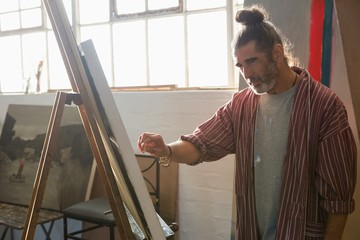 Mature man painting on easel