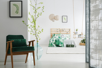 Dark green chair in bedroom