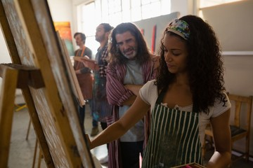 Smiling man looking at woman painting on artist canvas