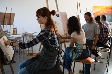 Artists painting while sitting on chair