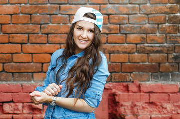 Young stylish woman in jeans clothes and a cap posing near a brick wall