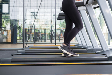 young woman execute exercise in fitness center. female athlete walking on treadmill in gym. sporty girl working out in health club.