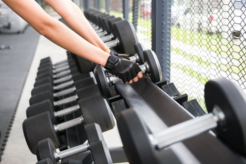 young woman execute exercise in fitness center. female athlete lift dumbbell in gym. sporty girl working out in health club.
