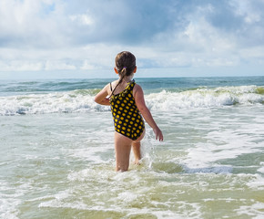 Child playing at the beach in the surf of the ocean