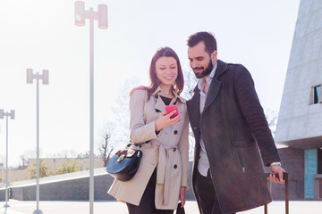 Man and woman travelling for business outside airport with mobile phone