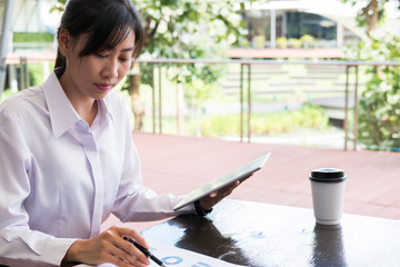 businesswoman with digital tablet & financial summary graph sitting outside office building. young asian woman analyzing investment charts outdoors. business people with coffee woking online