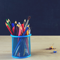 Stand for pen with pencils and colorful paper clips on wooden table, toned image. Concept of education or back to school
