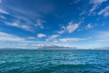 Iceland - Blue water of the ocean at the coast of the city of reykjavik with mountains