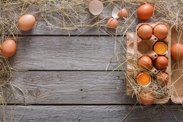 Fresh brown eggs in carton on rustic wood background