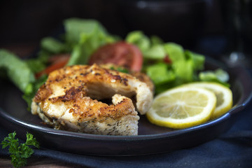 fried northern pike steaks with lemon, lettuce salad and tomatoes on a black plate, healthy low carb meal against a dark background, close up