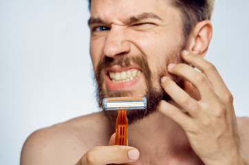 man with a beard holds a razor, close-up, portrait, emotions