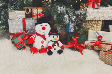 Cozy christmas background. Toy snowmen and presents under new ye