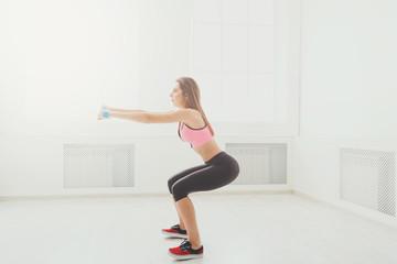 Young beautiful woman in sportswear doing squat