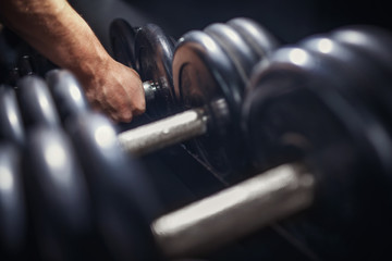 Man takes a dumbbell in the gym