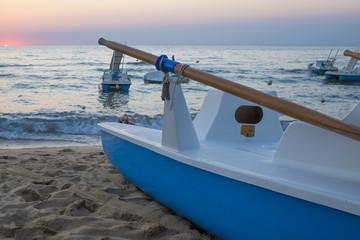 Due pedalò entrambi di colore bianco e azzurro uno a mare l'altro sulla spiaggia, durante il tramonto. Il sole ormai basso e vicino all'orizzonte dona le tonalita calde e il colore arancione al cielo.