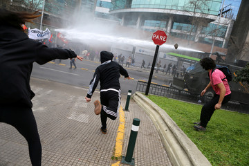 Demonstrators clash with riot police during a march called by students to request changes in the education system in Santiago
