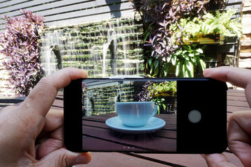 Smartphone in hands taking photo of a cup of coffee