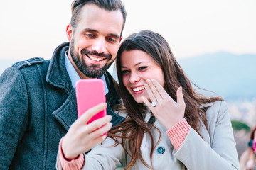 Newly engaged couple showing the ring and taking selfie with mobile phone
