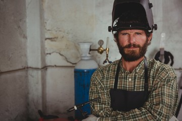 Confident welder sitting with arms crossed in workshop