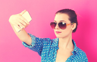 Young woman taking a selfie on a pink background