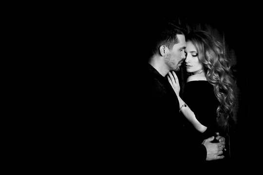 Beautiful couple in love hugging against black background. Studio black and white portrait photo of a girl blondes and a guy with short hair. Valentine's day. Loving married couple. Family happiness