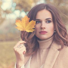 Autumn Fashion Model Woman with Wavy Hair and Fall Maple Leaf Outdoors